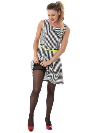 Model Released. Sexy Young Woman Raising Skirt Showing Stocking Tops photo
