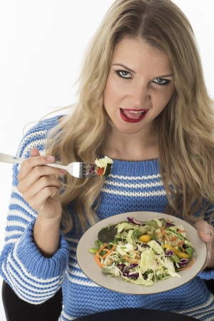 dissappointed: Model Released. Attractive Young Woman Eating Mixed Vegetables Stock Photo