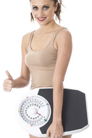 Model Released. Attractive Young Woman Holding Weighing Scales Stock Photo - 22243406