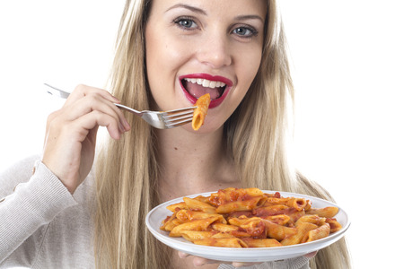 Model Released. Attractive Young Woman Eating Penne Pasta photo