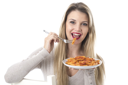 Model Released. Attractive Young Woman Eating Penne Pasta Stock Photo