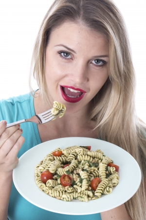 Attractive Young Woman Eating Spinach and Pine Nut Pasta photo