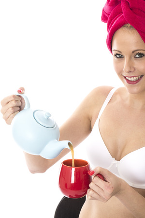 Model Released. Attractive Young Woman Pouring Tea from a Teapot photo