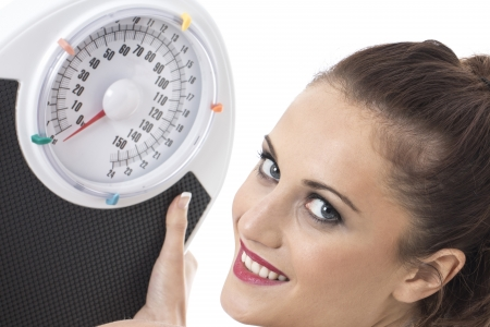 Model Released. Attractive Young Woman Holding Weighing Scales photo