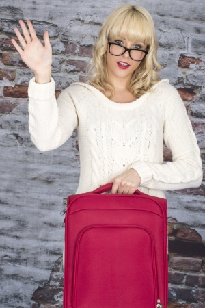 Model Released. Attractive Young Woman Holding a Suitcase Waving photo