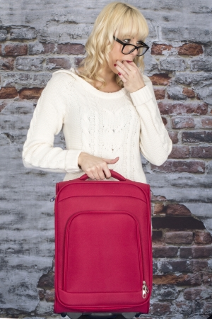 Model Released. Attractive Young Woman Holding a Suitcase Whistling photo