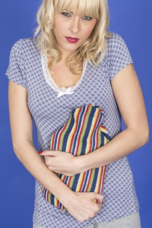 Model Released. Attractive Young Woman Holding a Hot Water Bottle Stock Photo - 23021870