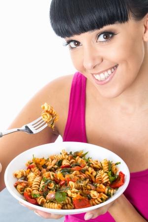 Young Woman Eating Pasta Salad Stock Photo