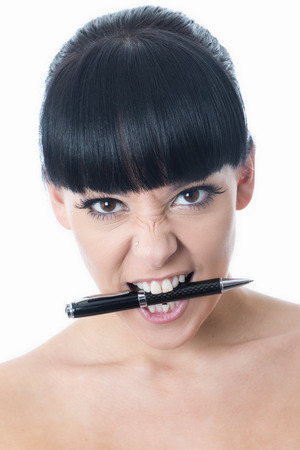 clenching teeth: Young Woman Holding a Pen in her Mouth Stock Photo
