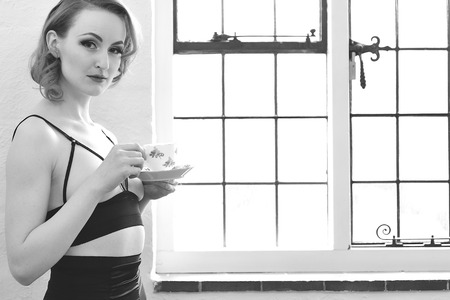 semi nude: Vintage Pin Up Model Drinking Tea Stock Photo