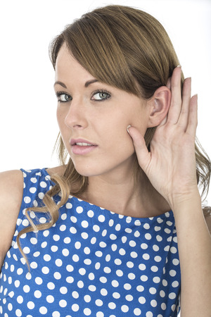 eavesdropping: Young Woman Wearing Blue Polka Dot Dress Eavesdropping Stock Photo