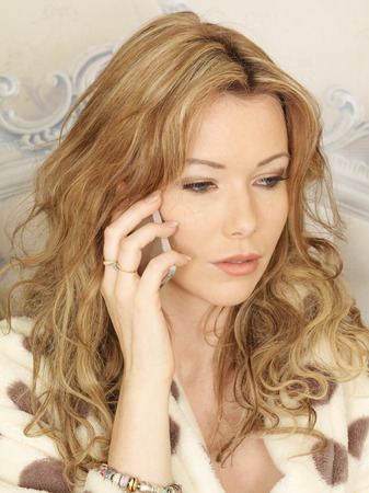 coy: Attractive Young Woman with a Mobile Telephone