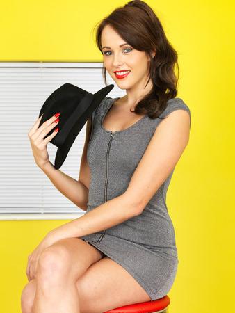 mini jupe: Attractive Young Woman court Mini-robe gris tenant un chapeau noir