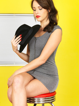 Attractive Young Woman Short Grey Mini Dress Holding a Black Hat photo
