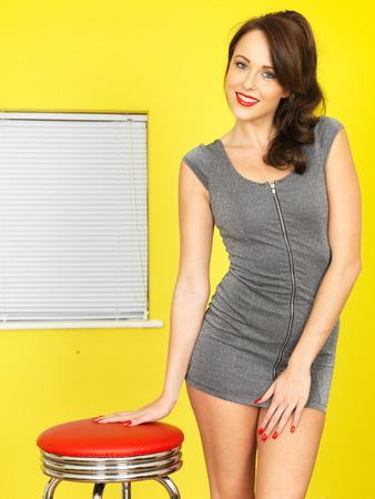 falda corta: Mujer feliz joven atractiva con un vestido mini corto gris