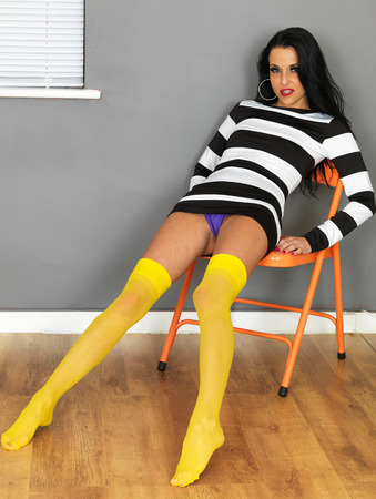 skirt up: Attractive Sexy Young Woman Wearing a Mini Dress and Yellow Stockings