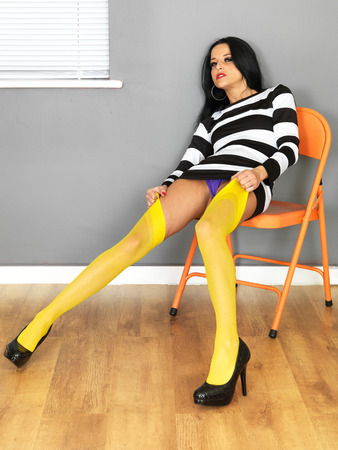 Attractive Sexy Young Woman Wearing a Mini Dress and Yellow Stockings