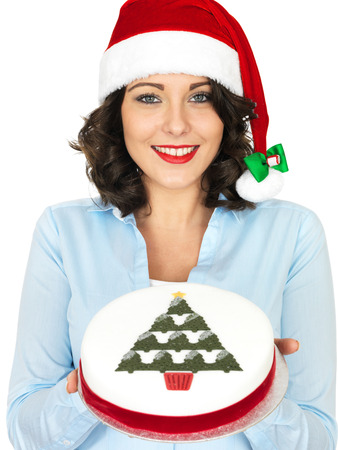 Young Woman in a Christmas Santa Hat Holding a Christmas Fruit Cake photo