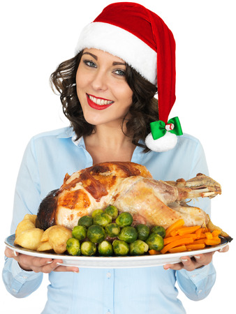 Attractive Young Woman in Christmas Santa Hat Holding Roast Turkey and Vegetables