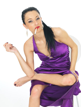 person smoking: Atractivo sexy mujer joven llevaba un vestido de coctel p�rpura