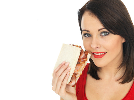 elevenses: Attractive Young Woman Eating a Bacon Sandwich