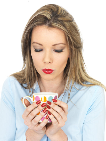 elevenses: Attractive Young Woman Drinking a Mug of Tea Stock Photo