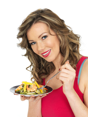 Healthy Young Woman Eating a Prawn and Mango Salad photo