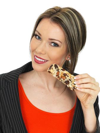 barra de cereal: Saludable Mujer de negocios joven que come una barra del cereal de desayuno