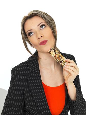 cereal bar: Saludable Mujer de negocios joven que come una barra del cereal de desayuno