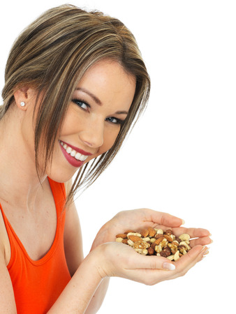 elevenses: Young Healthy Woman Holding a Handful of Mixed Nuts