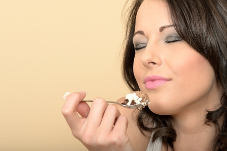 Attractive Beautiful Young Woman Portrait Looking at the Camera Eating a Chocolate Mousse Dessert photo