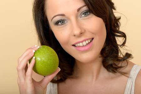Attractive Beautiful Young Woman Holding a Single Fresh Ripe Juicy Green Apple photo