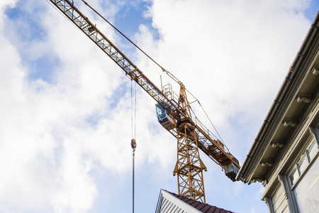 urban redevelopment: A Tower Crane Overlooking Urban Redevelopment Old Town Stavanger Norway against a Cloudy Sky