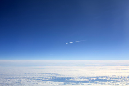 High Altitude Aircraft Lonely Vapour Trail Against a Blue Sky Above The Clouds