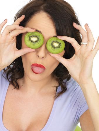 daft: Young Healthy Woman Holding Fresh Ripe Kiwi Fruit