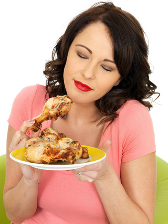 lean out: Young Healthy Woman Eating Cold Cooked Chicken Legs