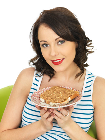 elevenses: Young Healthy Woman Holding Toast with Crunchy Peanut Butter Stock Photo