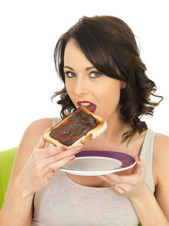 elevenses: Healthy Young Woman Holding Toast Spread with Marmite Stock Photo