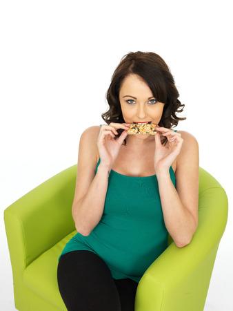 barra de cereal: Mujer joven sana que come una barra de cereales