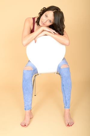 Attractive Lonely Looking Young Woman Sitting on a Chair Wearing Tight  Jeans photo
