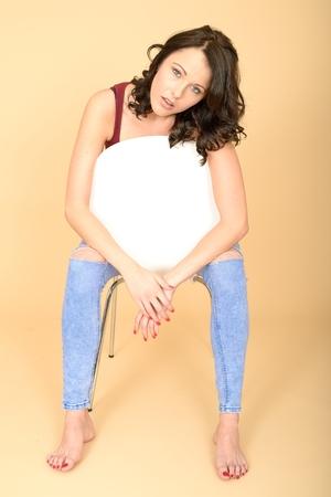 tight jeans: Attractive Solitaire Regarder Jeune femme assise sur une chaise, portant Tight Jeans