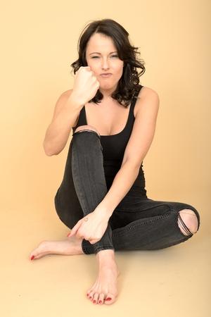 uñas pintadas: Atractivo sexy mujer joven vistiendo de negro jeans ajustados rasgados y chaleco Top Foto de archivo