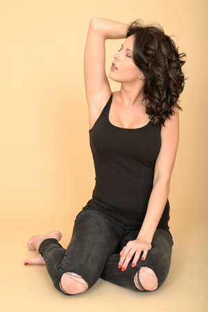 painted toes: Attractive Sexy Young Woman Wearing Black Tight Ripped Jeans and Vest Top