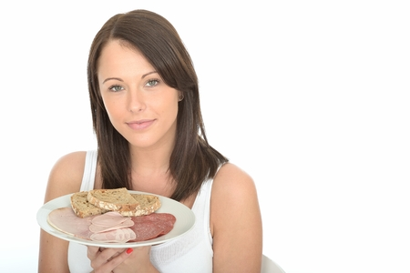 breakfast food: Healthy Attractive Young Woman Holding a Typical Norwegian Style Cold Buffet Breakfast of Meats and Bread