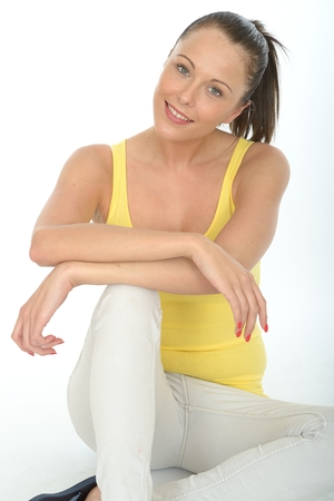 Happy Relaxed Portrait of a Confident Young Woman Facing the Camera Smiling Wearing a Bright Yellow Vest Top. photo