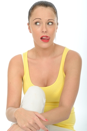pulling faces: Portrait of a Confused Worried Young Woman Pulling Faces Wearing a Bright Yellow Vest Top Stock Photo