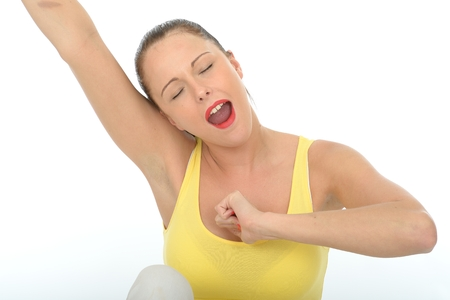 vest top: Attractive Young Woman Stretching and Yawning Wearing a Bright Yellow Vest Top Stock Photo