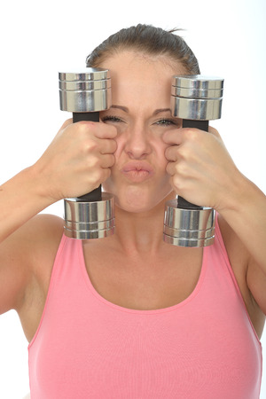 pulling faces: Healthy Young Woman Stressing While Training With Weights Looking at Camera Pulling Faces