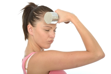 Healthy Young Woman Holding a Dumb Bell Weight to Her Forehead With Her Eyes Closed photo
