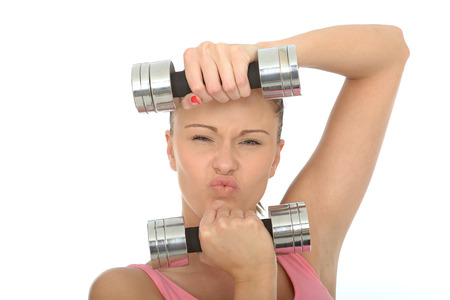 stressing: Healthy Young Woman Stressing While Training With Weights Looking at Camera Pulling Faces